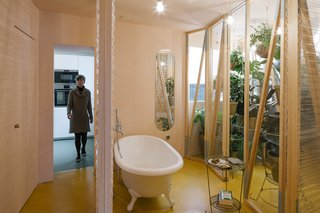 A Quirky Renovation Brings an Indoor Garden to the Center of Madrid - Photo 5 of 6 - The bathroom is located at the heart of the apartment, with sliding plastic doors of varying transparency that can be moved into a number configurations.