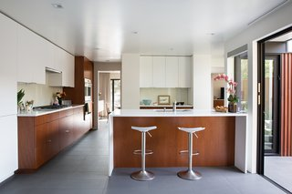 Not the Eichler Post-and-Beam Style You Know - Photo 3 of 7 - To match the original mahogany paneling, a set of new cabinets, crafted by by Benchmarc Woodworking, are installed in the kitchen. Dark bronze anodized doors from Fleetwood open up the space to the courtyard.