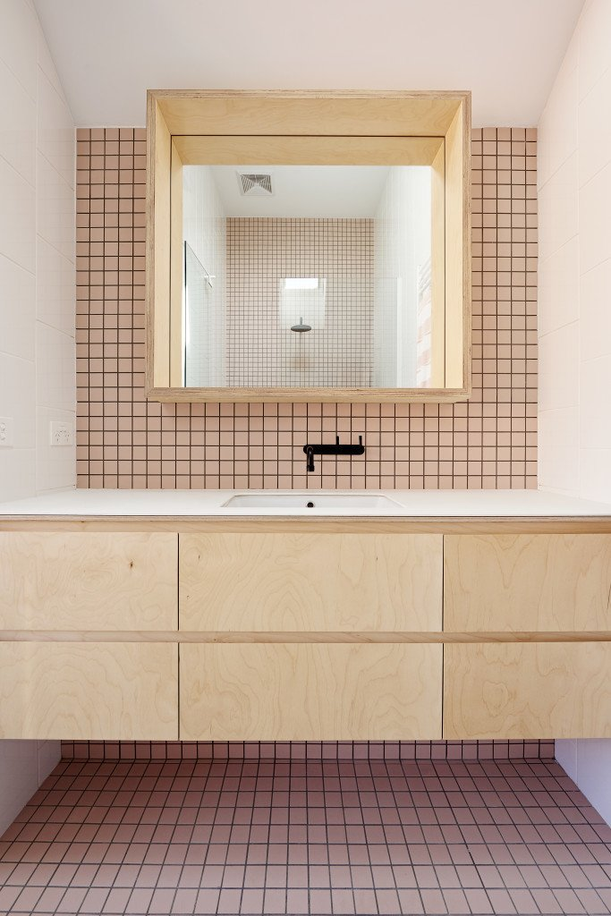 A second bathroom is clad in soft pink tile. All the matte-black fittings in the bathrooms and kitchen belong to the Yokato collection by Brodware.  Photo 9 of 11 in It Looks Like a Playland but This Home Works Hard