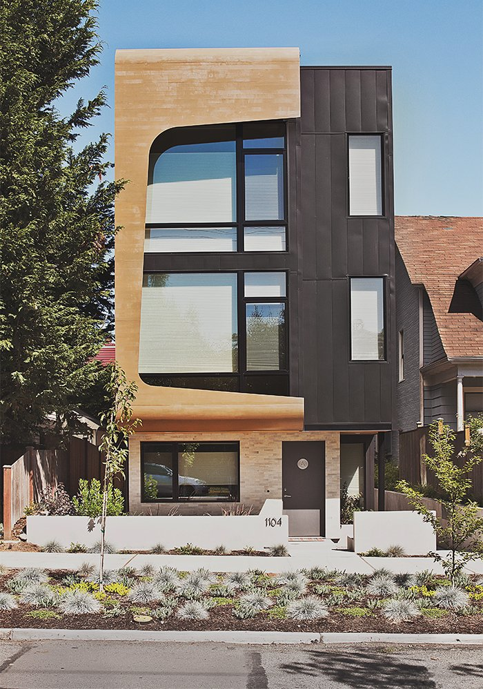 Architects Tiffany Bowie and Joe Malboeuf's Capitol Hill, Seattle, infill project was completed for $189 per square foot. Its street-facing facade is clad in prefinished siding from Taylor Metals, and cedar shaped and cut with CNC technology. The couple was inspired by the porthole windows of the Maritime Hotel in New York City, one of their favorite buildings.  Photo 2 of 12 in Three Families Comfortably Fit in One Slim Lot