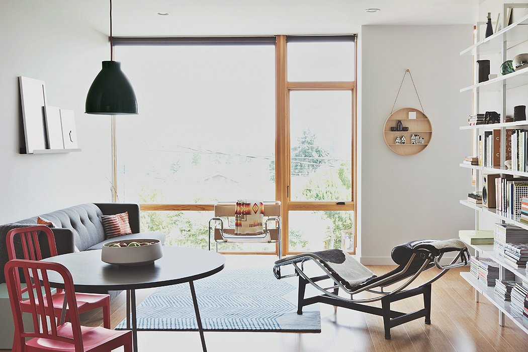 Bowie and Malboeuf's unit occupies three levels facing the property's backyard. The living-dining room has a mix of vintage pieces—a Wassily chair by Marcel Breuer and an LC4 chaise by Le Corbusier, Pierre Jeanneret, and Charlotte Perriand—alongside furniture from CB2.  Photo 3 of 12 in Three Families Comfortably Fit in One Slim Lot
