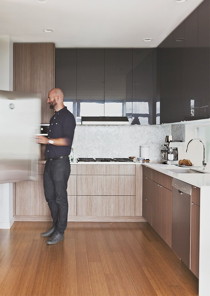 Malboeuf stands at a Fisher & Paykel refrigerator in the kitchen. He and Bowie shopped around to find appliances that balance cost and performance: the dishwasher is Bosch, the gas cooktop is Dacor, and the oven is Fagor. Walnut veneer clads the cabinets, and the floors are bamboo.