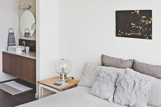 Three Families Comfortably Fit in One Slim Lot - Photo 5 of 11 - Bowie designed the nightstand, which acts as a prime perch for a vintage lamp her parents purchased in the Netherlands. The wall paint throughout the unit is Eider White by Sherwin-Williams.