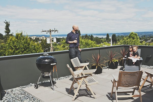 Rex folding rocker chairs from Design Within Reach are paired with black galvanized-steel planters from Ikea on the building's roof deck.  Photo 8 of 12 in Three Families Comfortably Fit in One Slim Lot