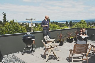 Three Families Comfortably Fit in One Slim Lot - Photo 7 of 11 - Rex folding rocker chairs from Design Within Reach are paired with black galvanized-steel planters from Ikea on the building's roof deck.