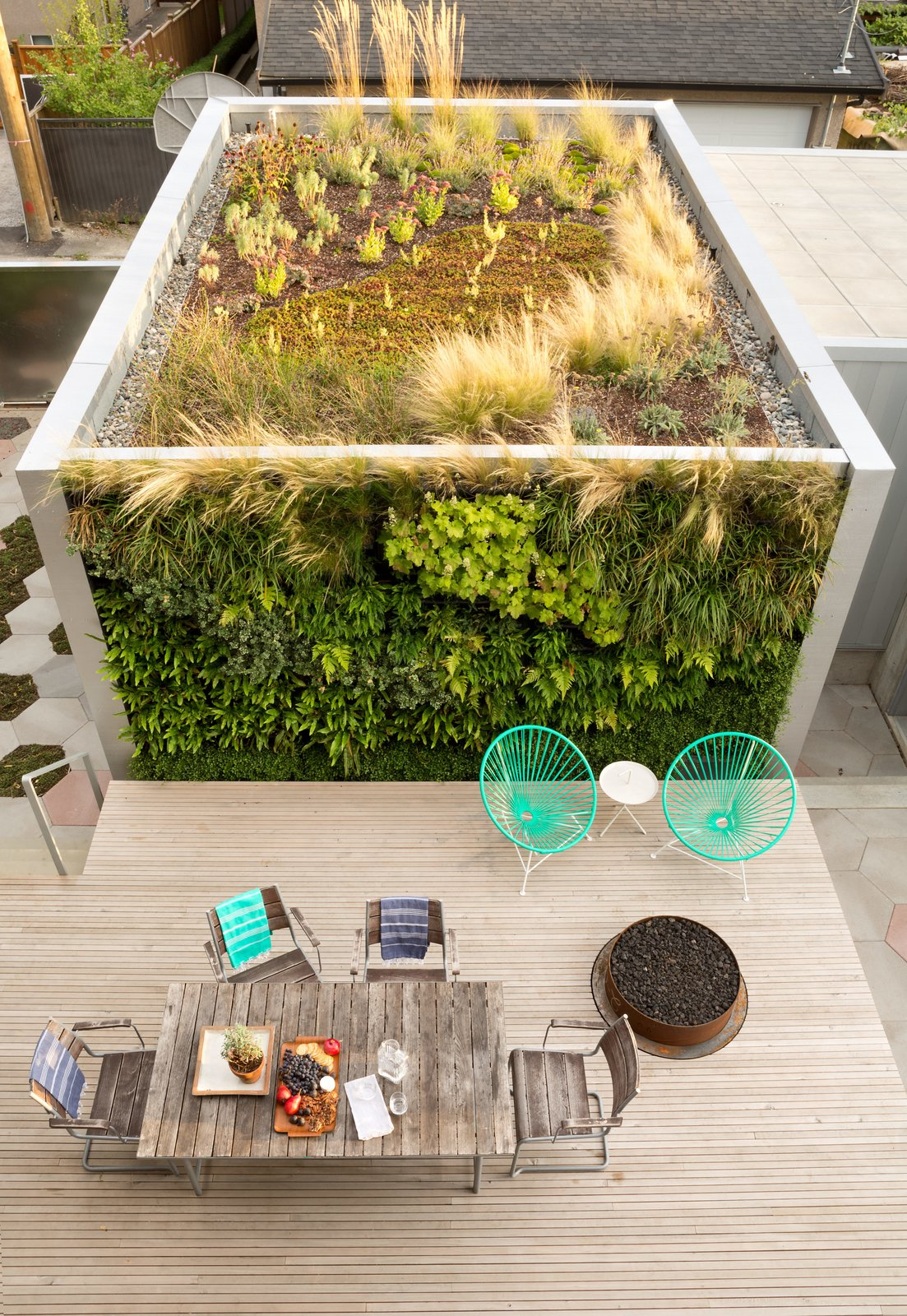 Designer Monica Berdin—who is married to architect Clinton Cuddington—worked with Aloe Designs to cover two sides of their backyard studio in drought-tolerant flora. A sheltered deck features a custom fire pit and a pair of turquoise Condesa chairs. Tagged: Rooftop, Wood Patio, Porch, Deck, Large Patio, Porch, Deck, Exterior, and Green Roof Material.  Photo 24 of 25 in 25 Blissful Backyards from A Wild Garden Leaps Off the Walls of This Backyard Build