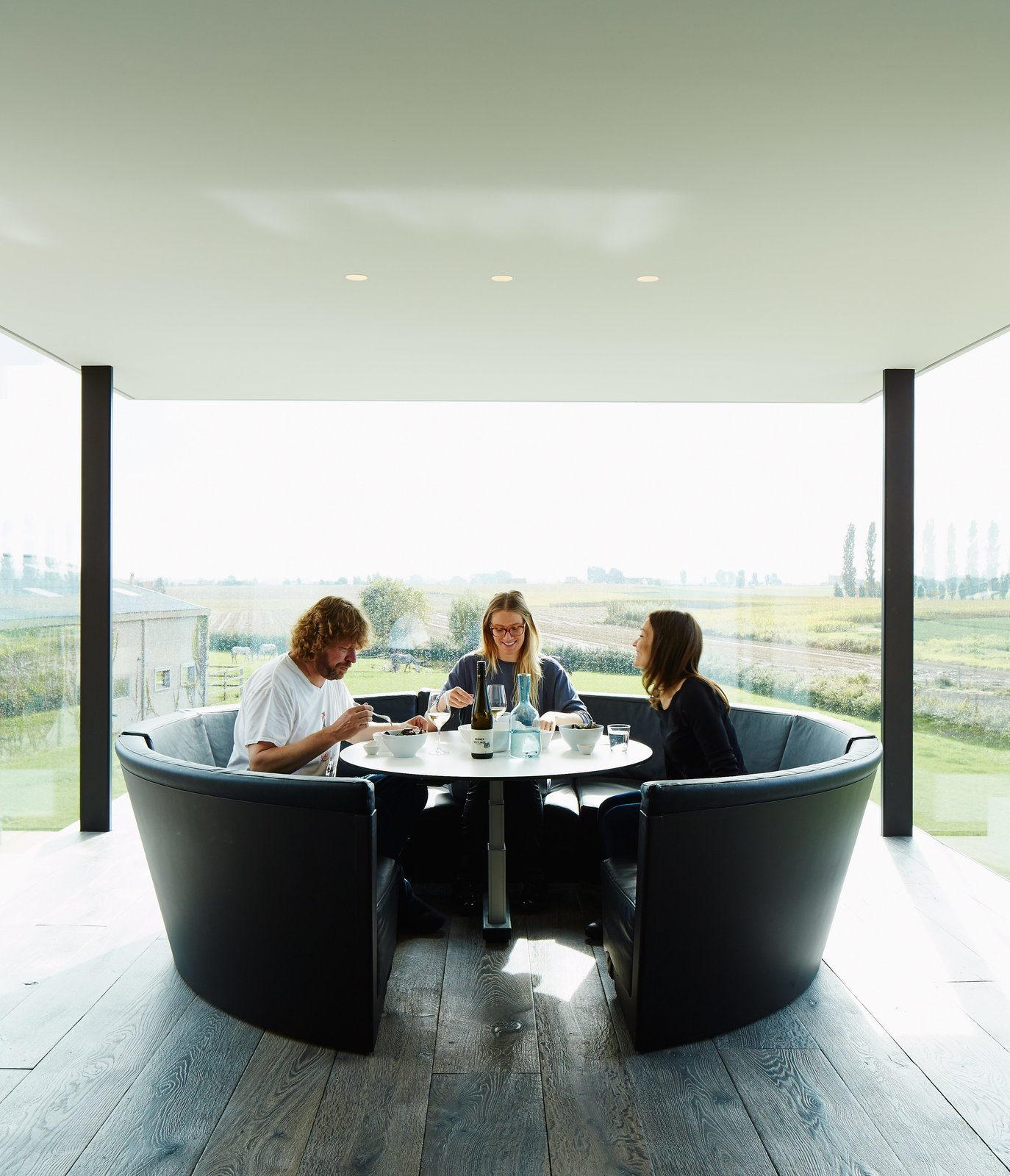 Wynants lives in the house with his wife, Hilde Louwagie, and their three children. His own circular seating design, Kosmos, is in the kitchen. Tagged: Dining Room, Table, Recessed Lighting, Dark Hardwood Floor, and Bench.  Photo 3 of 11 in A Kubrick-Esque Farmhouse Kicks Its Fossil Fuel Habit