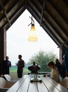 A Kubrick-Esque Farmhouse Kicks Its Fossil Fuel Habit - Photo 6 of 10 - An open-air terrace off the kitchen features a Marina table and Captain chairs from Extremis.