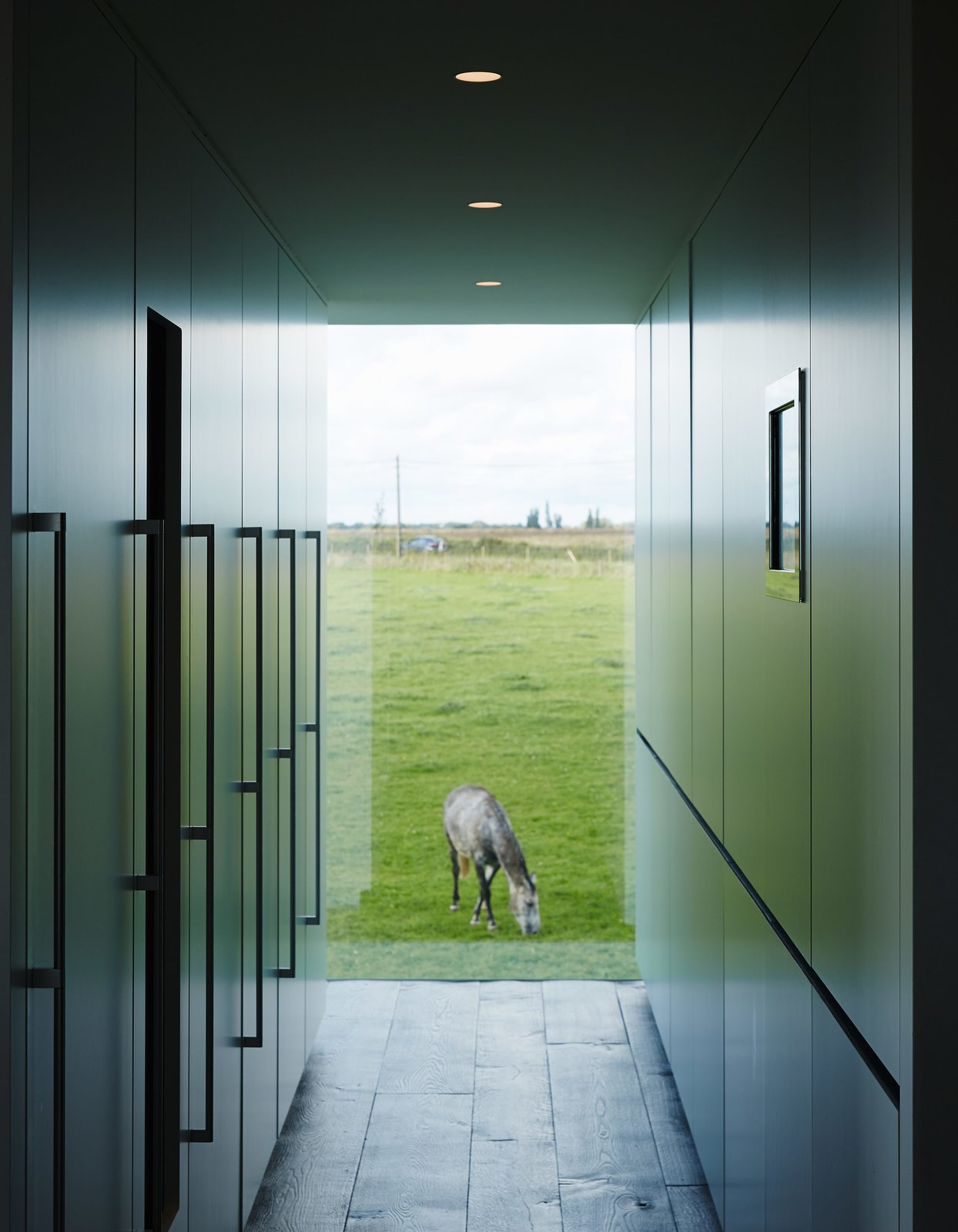 Discreet kitchen storage, which conceals the refrigerator, a wine cooler, the freezer, recycling, and cleaning materials, complements a view of one of the family's five horses. Tagged: Hallway and Dark Hardwood Floor.  Photo 9 of 11 in A Kubrick-Esque Farmhouse Kicks Its Fossil Fuel Habit