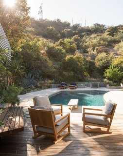 25 Blissful Backyards - Photo 8 of 25 - Low retaining walls form a subtle barrier between the backyard and the surrounding vegetation. Mandy Graham designed the armchairs and lounges.
