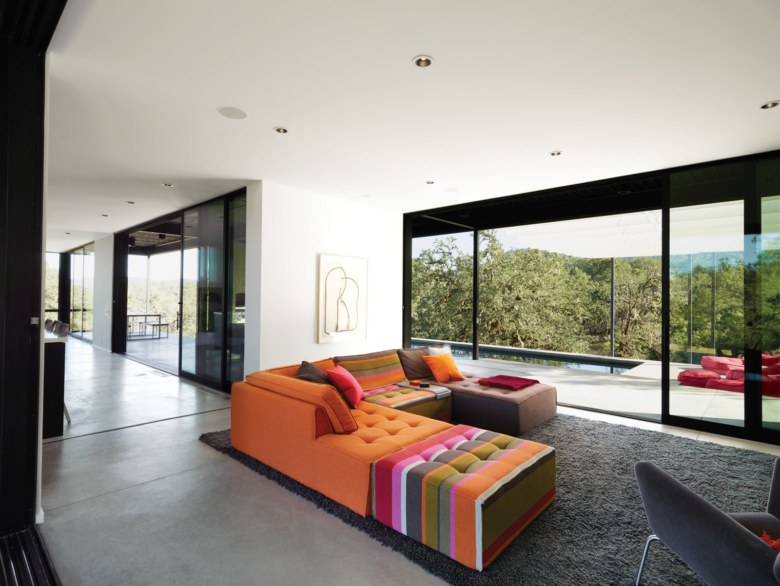 The Mikado 2 sofa by Hans Hopfer for Roche Bobois is a bright and cheery centerpiece in the otherwise sedate living room. The nubby wool Photon rug from Design Within Reach warms up the expanse of concrete. The framed drawing is by the Los Angeles–based artist Daniel Brice. Huge sliding doors open the house to the outdoors and virtually double the Burtons' living space.