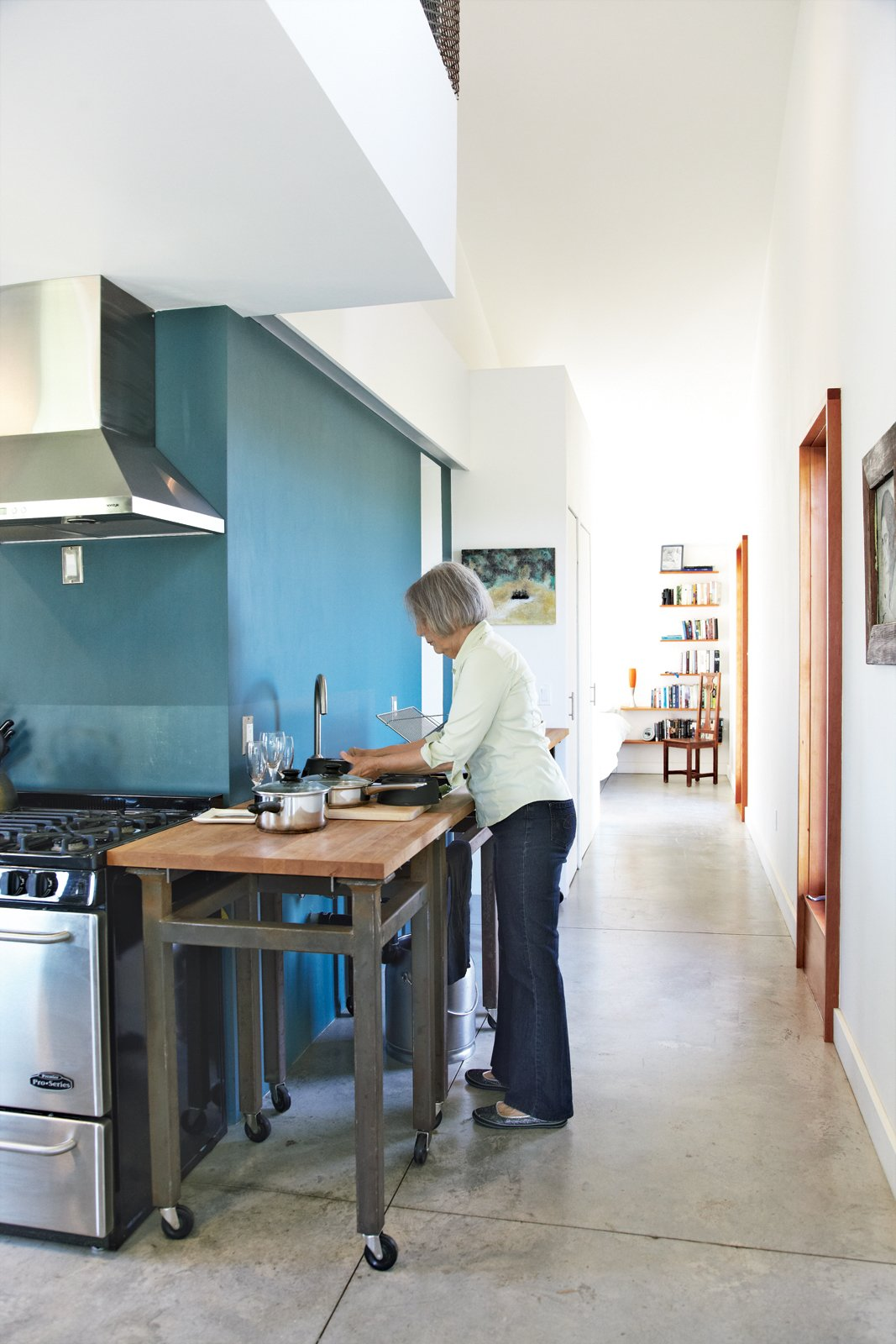 Though small, Treanor's house feels spacious thanks to an open kitchen and a tranquil mezzanine. Tagged: Kitchen, Concrete Floor, and Wood Cabinet.  Photo 7 of 11 in An Off-Grid Home That Relies on the Sun and the Wind
