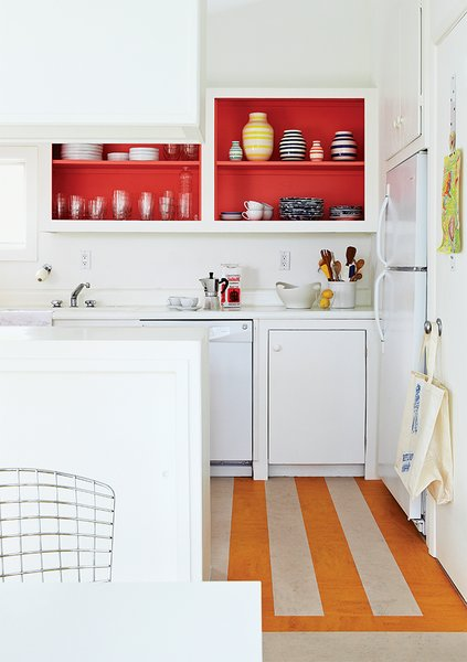 In the kitchen, Angle removed the cabinet doors and applied a coat of Poppy Red paint by Benjamin Moore, and put down a striped linoleum floor to brighten the space.
