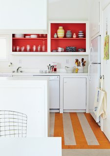 How a Smart Interior Design Saved This House - Photo 5 of 9 - In the kitchen, Angle removed the cabinet doors and applied a coat of Poppy Red paint by Benjamin Moore, and put down a striped linoleum floor to brighten the space.