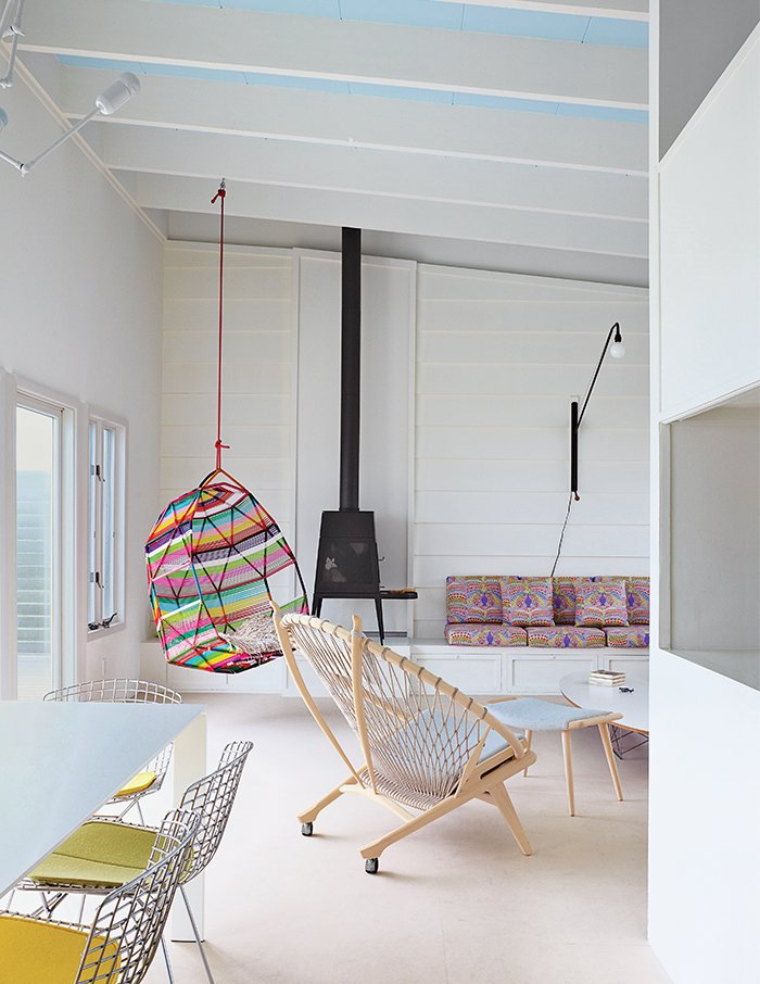 Alexandra Angle transformed a beachside cabin into a colorful retreat for a college friend and her family. The living area features a PP130 Circle Chair by Hans Wegner and a Shaker wood stove by Antonio Citterio with Toan Nguyen for Wittus. A Tropicalia Cocoon hanging chair by Patricia Urquiola complements the fabric from Liberty that Angle used for the cushions on the built-in banquette. Tagged: Living Room and Chair.  Photo 4 of 9 in How a Smart Interior Design Saved This House