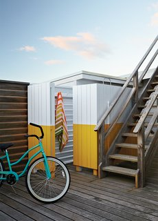 The wood screen concealing the outdoor shower was painted yellow and white, matching the color scheme in the guest bathroom.