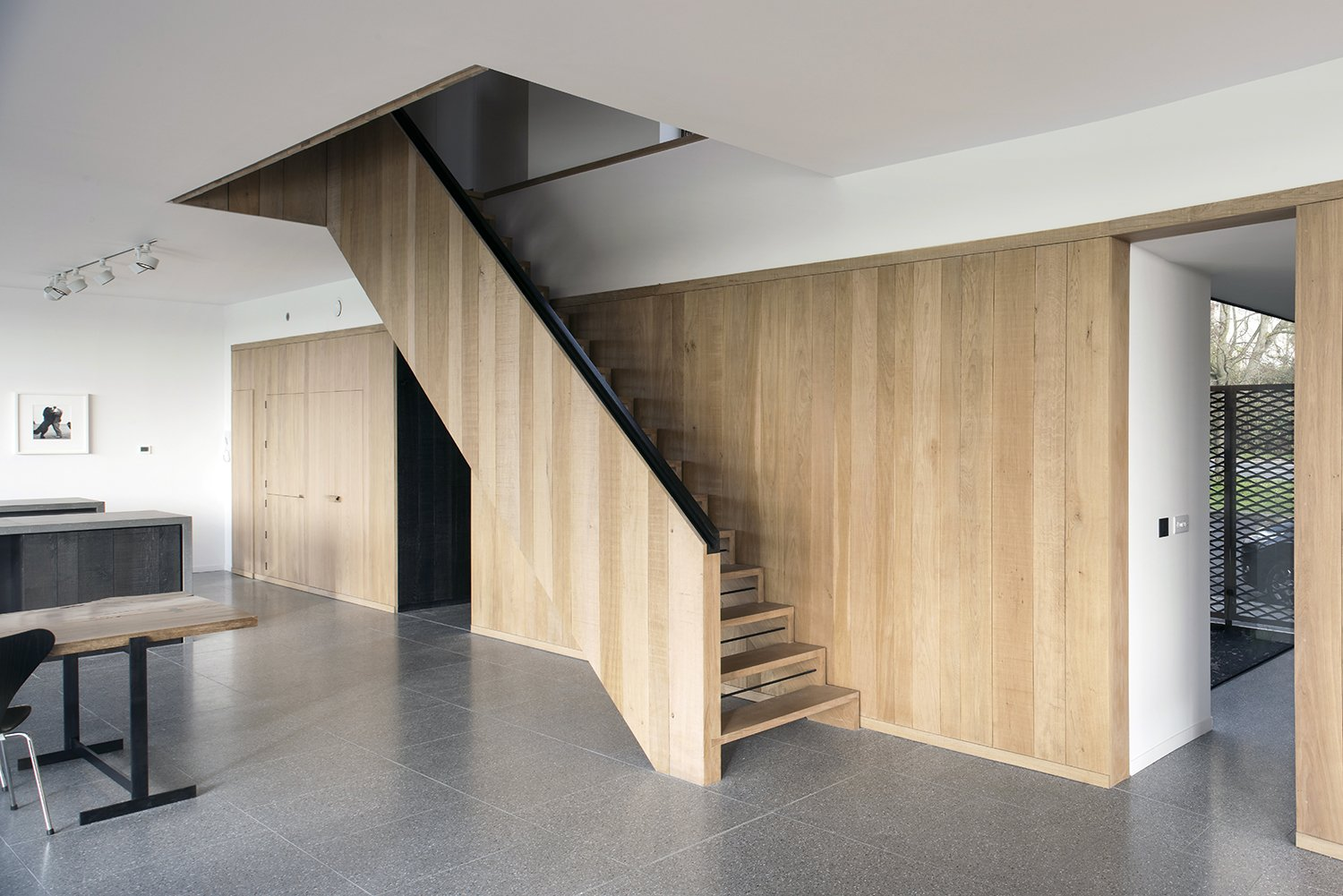 A palette of natural materials is employed in both the interior and exterior. An oak wall and staircase, designed by Jeremy Pitts, join a floor made of gray terrazzo tile.