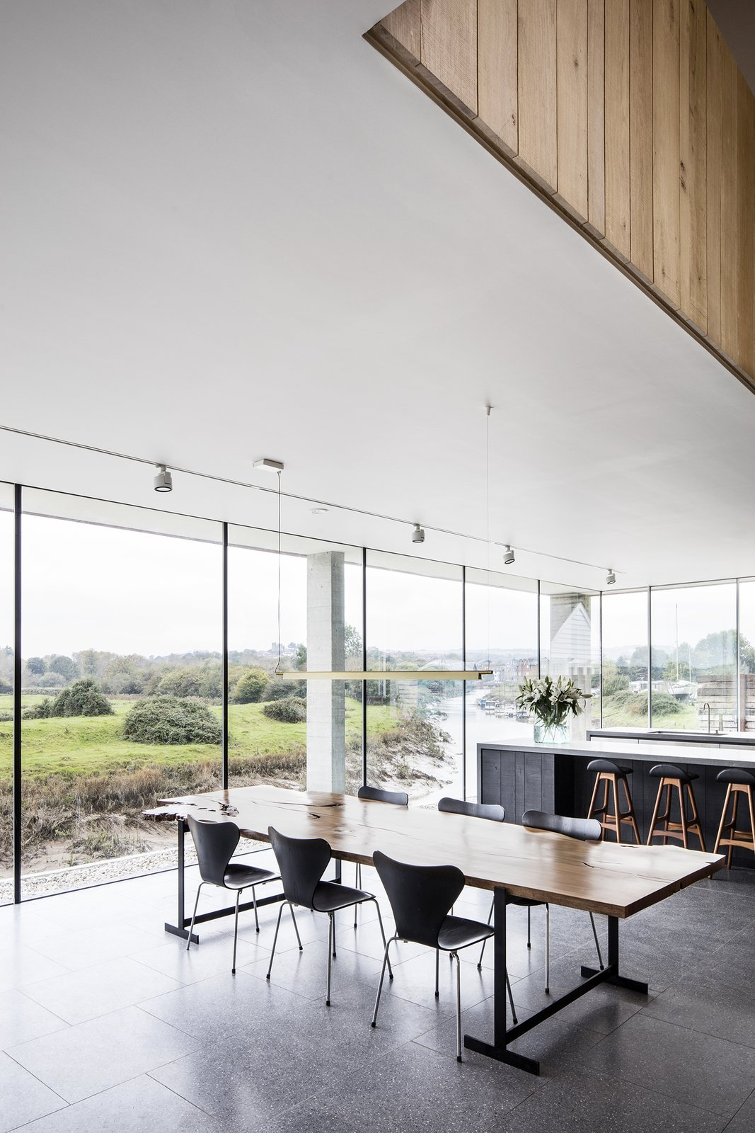 A young family resides in the five-bedroom house: Stephen, who works in advertising, Anita, a lawyer who works in financial services, two young children, and two basset hounds. The open-plan ground level is meant to be flexible, and its layout can be adapted as the family's needs change over time. Floor-to-ceiling windows overlook the river that runs right by the structure.