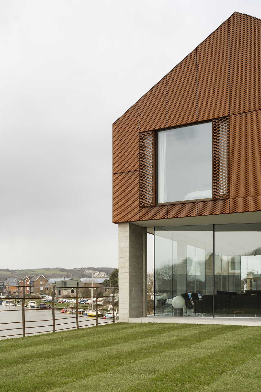 The upper story is clad in a decorative rainscreen of Cor-Ten steel mesh, chosen in part for its tone, which complements the red clay brick used locally.