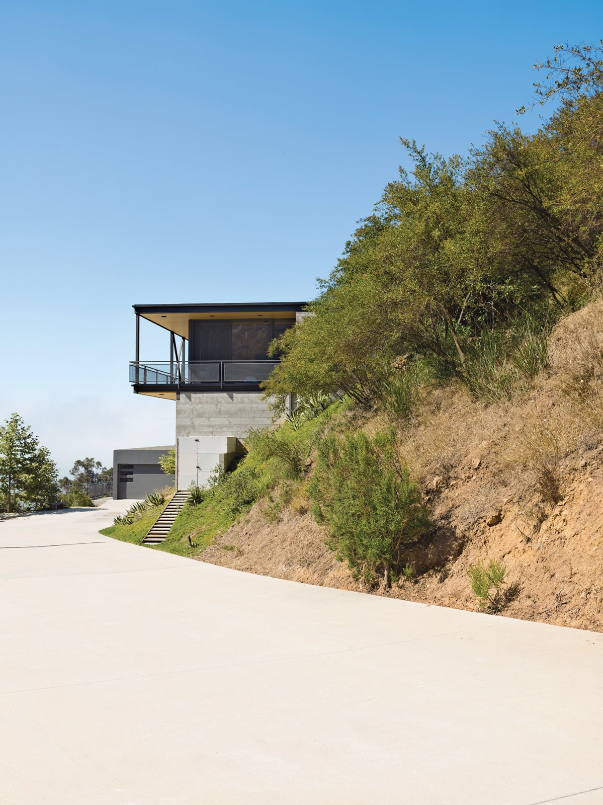 To deal with a Malibu site's sharp incline, architect Bruce Bolander set the steel, concrete, and glass house on caissons. A deep wraparound porch nearly doubles the home's living space and offers the ideal perch for outdoor dining and taking in spectacular views of the surrounding canyon. The garage serves as resident Dave Keffer's home office. Tagged: Exterior, House, Concrete Siding Material, and Flat RoofLine.  Photo 2 of 9 in This High-Flying Home Tackles a Sharp Slope