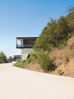This High-Flying Home Tackles a Sharp Slope - Photo 1 of 8 - To deal with a Malibu site's sharp incline, architect Bruce Bolander set the steel, concrete, and glass house on caissons. A deep wraparound porch nearly doubles the home's living space and offers the ideal perch for outdoor dining and taking in spectacular views of the surrounding canyon. The garage serves as resident Dave Keffer's home office.