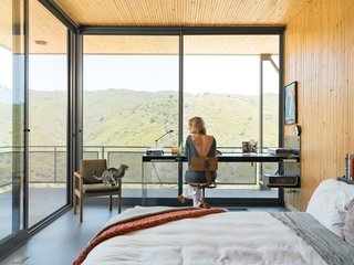 This High-Flying Home Tackles a Sharp Slope - Photo 3 of 8 - Bolander designed the custom steel desk where Wright works, as well as the bedside table, fashioned from a speaker tower base and a slab of white oak. The desk chair and table lamp are vintage; the bed linens are from Garnet Hill and Ikea. The floor-to-ceiling sliding glass doors from Metal Window Corporation open the entire corner of the room up to the outdoors.