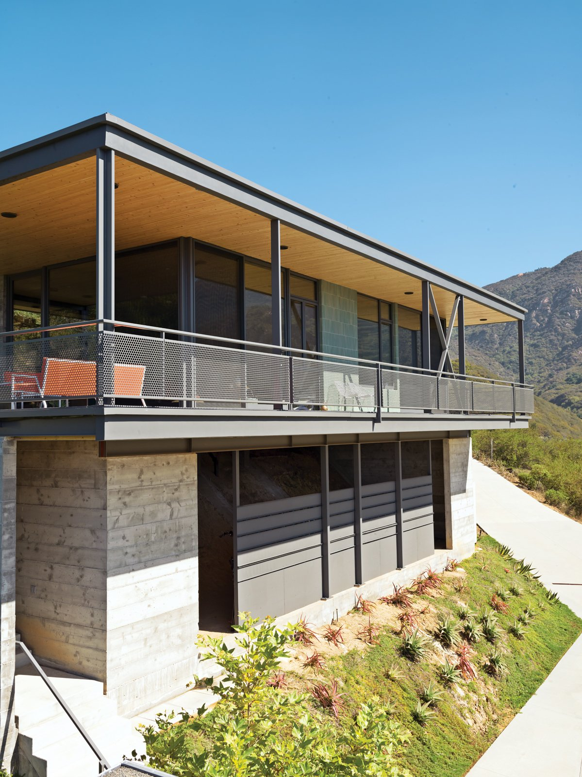 Fir slats on the wall and ceiling run through to the outdoors, visually expanding the space. Tagged: Exterior, House, Flat RoofLine, Concrete Siding Material, and Metal Siding Material.  Photo 9 of 9 in This High-Flying Home Tackles a Sharp Slope