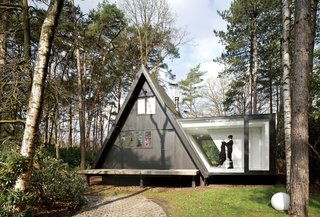 This Minimal Addition Looks Magical in the Belgian Forest - Photo 1 of 4 - Adding 290 square feet to this already small (just 566 square feet) black A-frame in Brecht, Belgium, was all the local building ordinances allowed, but the architects at dmvA found that a single wing extended out to the side gave resident Rini van Beek all the storage and living space that she needs.