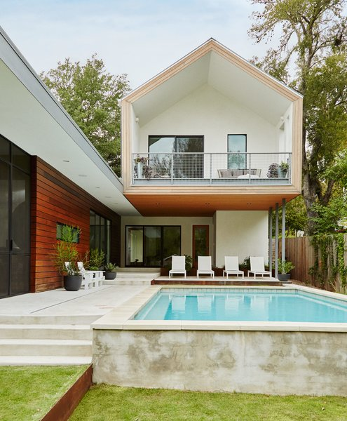 Architect Burton Baldridge's design for a house in Austin features a cantilevered upper volume with a gabled profile that was in part inspired by the work of Dutch architects MVRDV. It juts out over the patio, outfitted with chaise longues by Harbour Outdoor and Adirondack chairs by Loll.