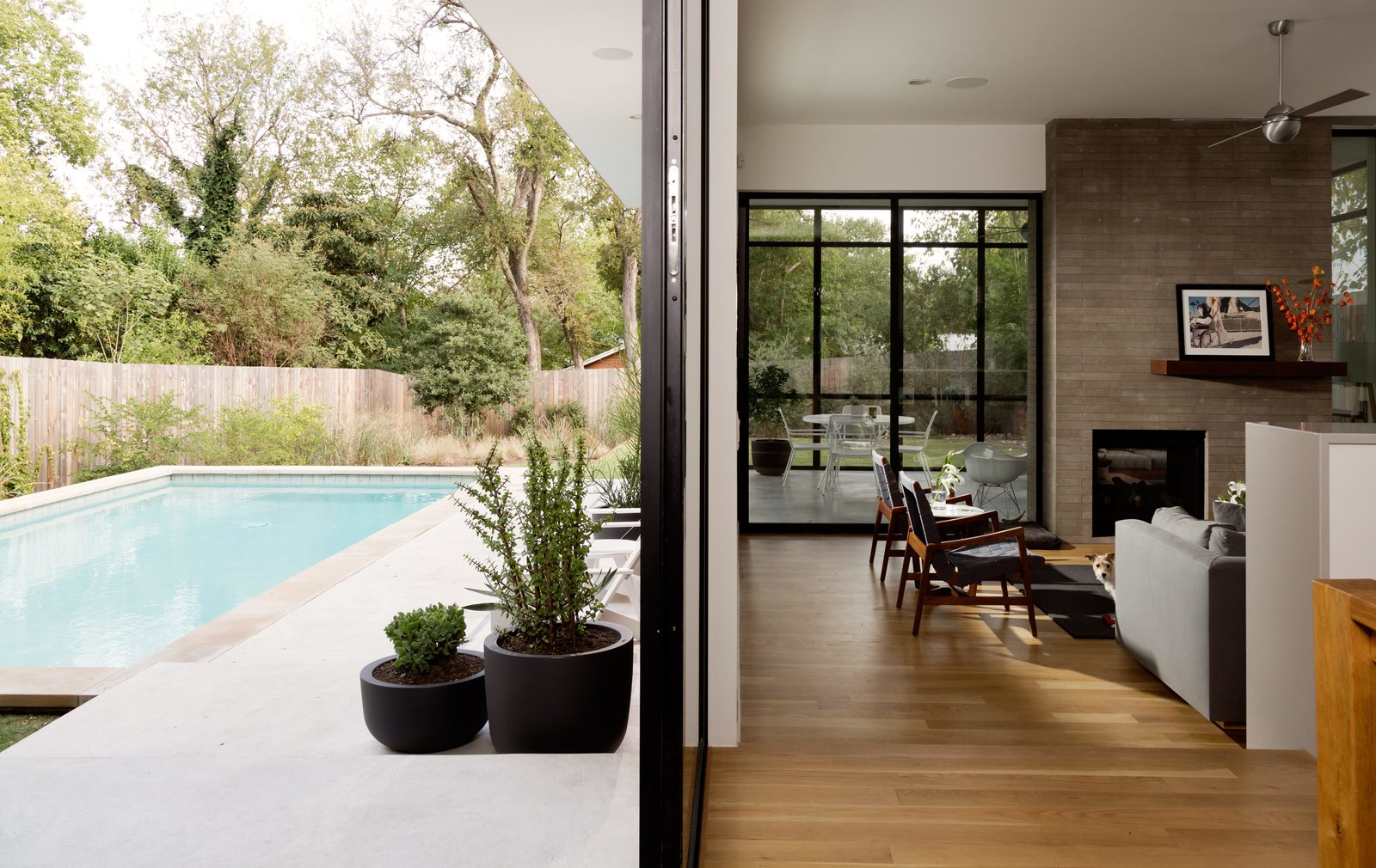 A double-sided fireplace serves as a way to unite the screened-in porch to the house's main, open-plan living area. Tagged: Outdoor, Large Pools, Tubs, Shower, Concrete Pools, Tubs, Shower, and Swimming Pools, Tubs, Shower.  Photo 4 of 6 in Refreshed Take on the Gable Shines in Austin's Building Boom