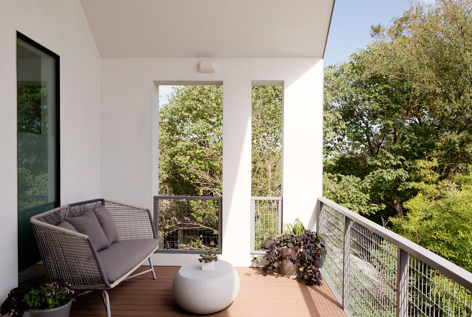 A covered deck off the master bedroom with a Huron sofa by West Elm provides another spot to take in the city's pleasant days. Tagged: Outdoor, Metal Fences, Wall, and Wire Fences, Wall.  Photo 5 of 6 in Refreshed Take on the Gable Shines in Austin's Building Boom