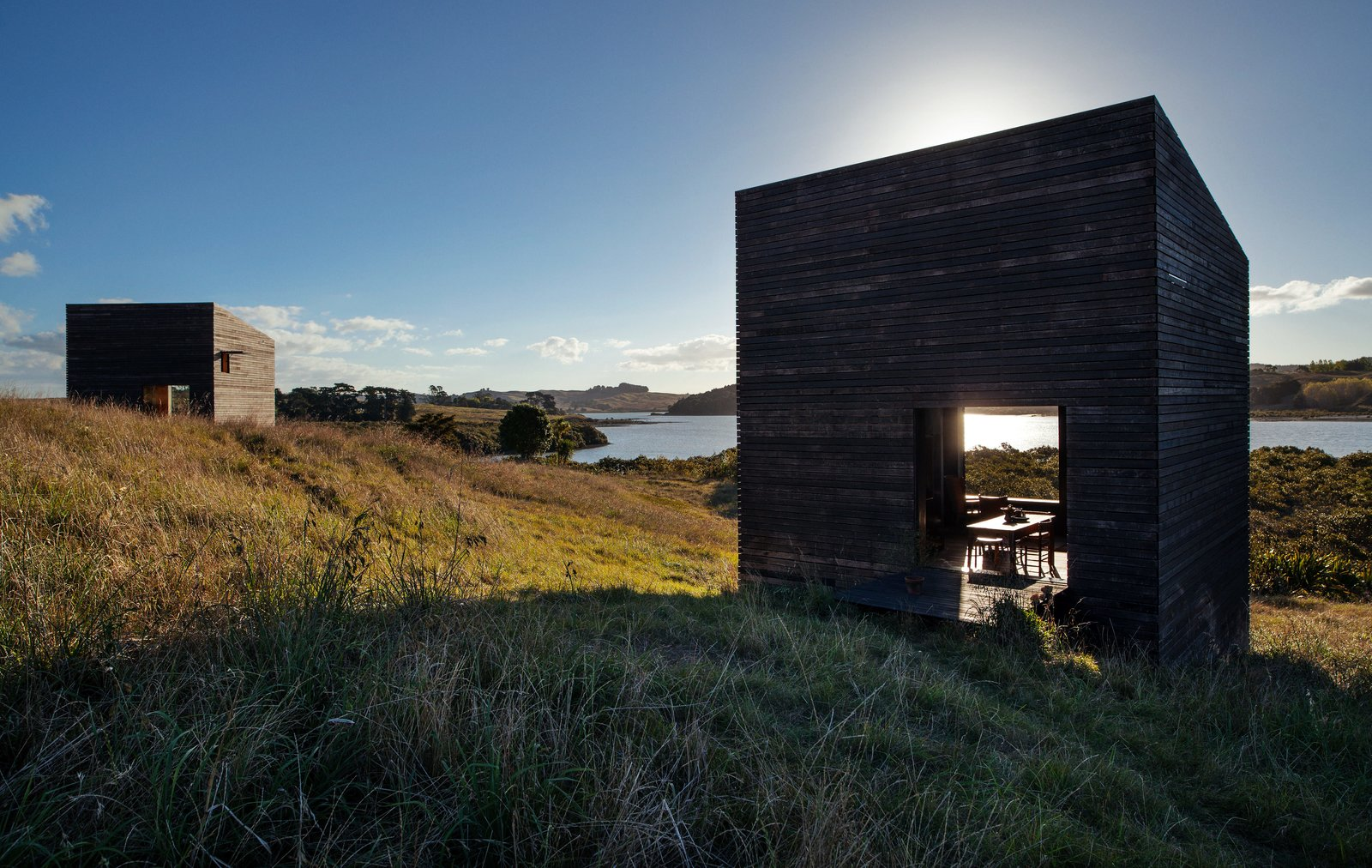 Before building on the North Island of New Zealand, two friends spent years replanting the site. The 290-square-foot structures Cheshire Architects designed for them reject the local trend of oversize beach houses—instead, they sit on the landscape like a pair of minimalist sculptures. Tagged: Shed & Studio and Living Space.  Photo 2 of 7 in Two Tiny Cabins Chose Simplicity Over Size