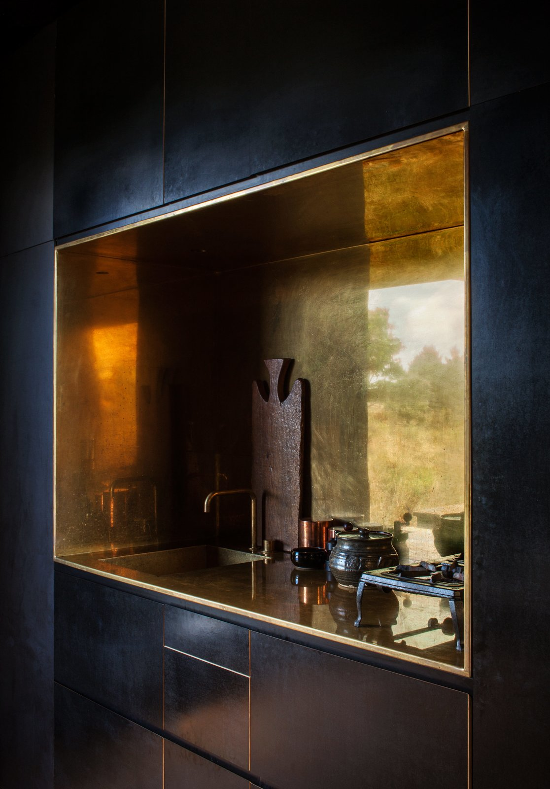 "The kitchen's brass-lined niche, with a matching tap by Arne Jacobsen for Vola, contrasts the otherwise spare, black formply interior of one of the cabins. ""We wanted to introduce one piece that was deliberately special, that would build drama between the humility of the unfinished and the very precise polish of this one object,"" says designer Nat Cheshire. Tagged: Kitchen and Undermount Sink.  Photo 3 of 7 in Two Tiny Cabins Chose Simplicity Over Size"
