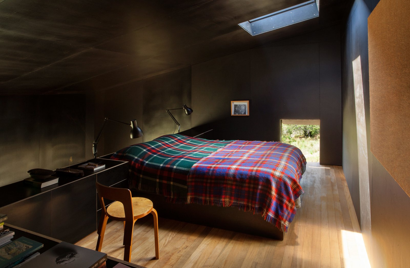 """The formply used to line the black interior creates a """"small, inky bubble of space,"""" Cheshire says. """"It's incredibly calm and quiet as a consequence."""" His firm designed the built-in bed and cabinetry. The two Type 75 lamps are by Kenneth Grange for Anglepoise, and the Chair 65 is by Alvar Aalto. Tagged: Bedroom, Bed, Chair, Lamps, and Night Stands.  Photo 5 of 7 in Two Tiny Cabins Chose Simplicity Over Size"""