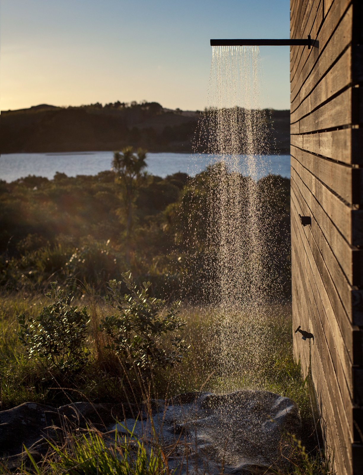 "Just like the interior, the outdoor shower is an exercise in reduction and contrast: It's merely a boulder placed under a showerhead on the side of the building. ""If you really strain your eyes, you can see perhaps one other house,"" Cheshire says of the vista.  Photo 7 of 7 in Two Tiny Cabins Chose Simplicity Over Size"