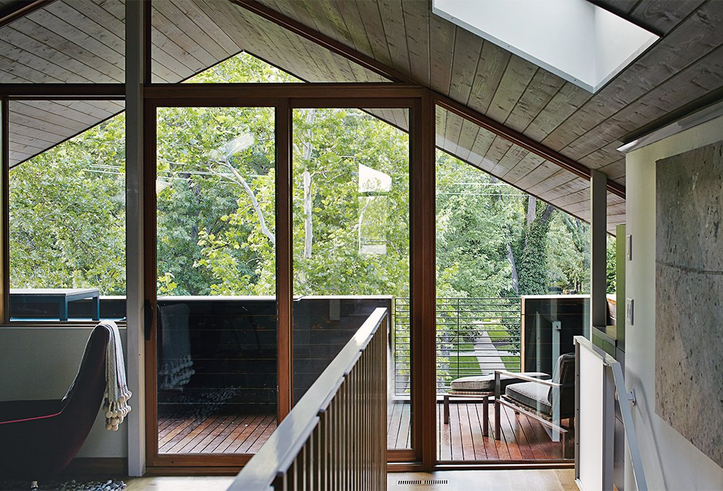For the deck that overlooks the backyard, they installed LED Outdoor Floodlights. Shown here is their third-floor office that looks out to these outdoor spaces.  Photo 11 of 13 in These Modern Parents Show How Invaluable Technology Can Be