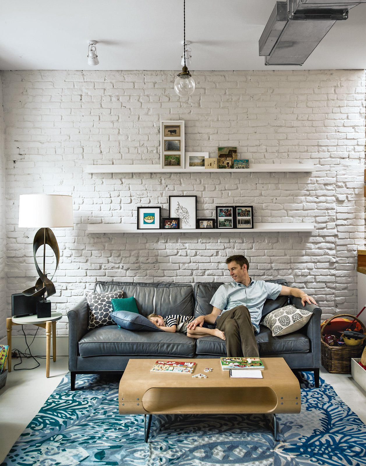 """Bischoff's team retained the exposed brick on the interior, painting much of it white to help the space reflect sunlight. """"There was an interest in having an open, more contemporary layout, but we still wanted some sense of living in this building that's 100 years old,"""" Bischoff says. """"That motivated us a lot to keep the brick. It's a very subtle echo of what the house originally was."""" Enclosing the ductwork would have forced the architects to lower the ceiling or install a subpar air-conditioning system. So it was left exposed, contributing to the floor's loftlike atmosphere. New meets old with the furnishings as well: An antique barbershop pendant provides contrast to a sculptural lamp and a rug from Anthropologie. Investment buys were made with budget in mind, like the leather sofa scored at ABC Carpet & Home's outlet store. Tagged: Living Room, Sofa, Coffee Tables, End Tables, Pendant Lighting, Rug Floor, and Table Lighting.  Photo 6 of 9 in The Brownstone Baked to Perfection"""