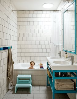 """Bathroom: A creative way of cutting costs is on display in son Nate's bathroom, where the wall tiles are arranged in a whimsical, irregular pattern making use of slim sections of tile cut for transitions and corners. """"We came up with a pattern that could incorporate random sizes so we were able to order the exact amount of tile that we needed,"""" Bischoff says. """"It allowed us to get the most out of the tile price because there wasn't that 20 percent that [would normally go] into the landfill."""" The two-bowl sink is the Vitviken model from Ikea; it's topped with a chrome Hansgrohe faucet and accented by Ikea's Godmorgon medicine cabinets customized by MADE."""