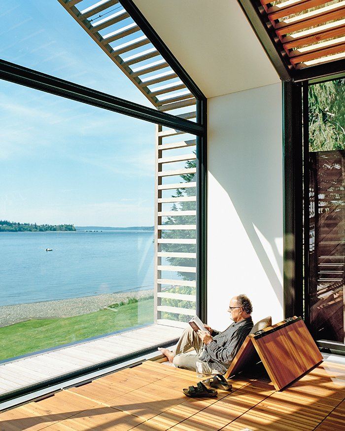 The Trues host parties in the glass-walled structure, located steps from their vacation home, or they escape to it to catch some rays and read a book. Bill reclines on cushions hidden under the reclaimed-fir floorboards that are propped up with Sugatsune hinges. Tagged: Windows, Metal, and Picture Window Type.  Photo 7 of 10 in A Former Garage Hosts the Best Parties