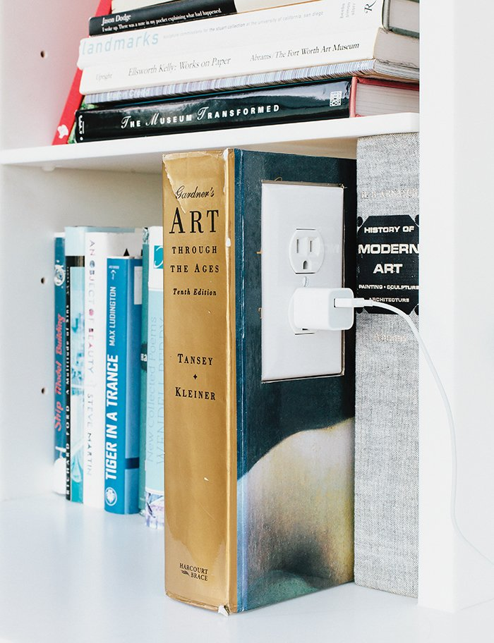 """The garage is an exercise in """"hide and reveal."""" The Corian shelf features an outlet in a converted book, a detail that brings delight to a mundane task. """"We wanted to make the experience of plugging in a phone or computer joyful,"""" Grizzle says. Tagged: Storage Room.  Photo 4 of 10 in A Former Garage Hosts the Best Parties"""