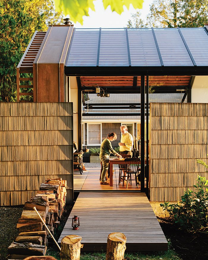 To reference the original structure and to offer privacy, Grizzle left two of the shingled walls standing. The building, accessed by a cedar deck, opens to its surroundings via a sliding glass wall by Fleetwood and a bifold steel-and-glass garage door from Wilson Doors. Tagged: Outdoor, Small Patio, Porch, Deck, and Wood Patio, Porch, Deck.  Photo 5 of 10 in A Former Garage Hosts the Best Parties