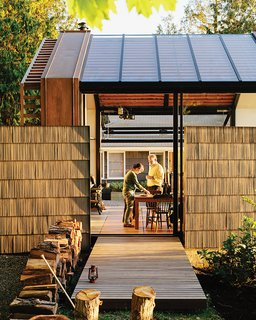 To reference the original structure and to offer privacy, Grizzle left two of the shingled walls standing. The building, accessed by a cedar deck, opens to its surroundings via a sliding glass wall by Fleetwood and a bifold steel-and-glass garage door from Wilson Doors.
