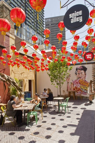 """Spice Alley's four outdoor eateries enliven the laneway under a canopy of red lanterns. """"Resurrected building frontages spill out onto the street and provide a streetscape that is activated by day and night by conversation, creative hustle, and culture,"""" says landscape architect Mike Horne of Turf Design Studio."""