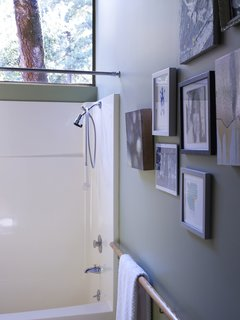 You Don't Have to Just Be at Your Desk When Working from Home - Photo 13 of 19 - A salon-style hanging of art and the wooden handrail-cum-towel rack give the bathroom a handful of subtly stylish touches.