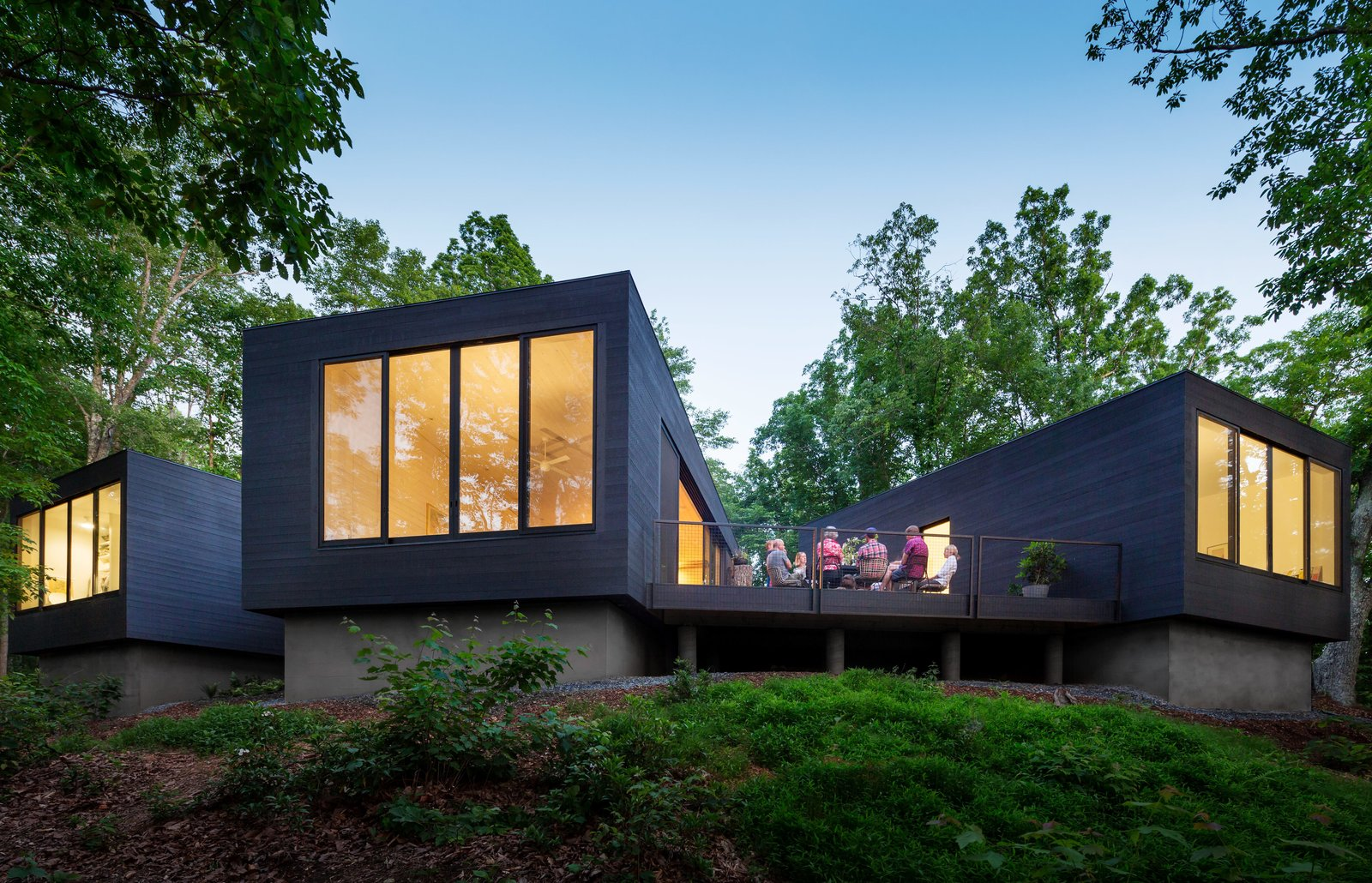 "Desiring a home in a natural setting for their three sons, ages 5, 9, and 10, architects Katie and Danny MacNelly built a three-volume residence near Virginia's James River. With a focus on outdoor social spaces, Katie likens the overall program to ""loose coals around a campfire."" Tagged: Exterior, Wood Siding Material, Concrete Siding Material, and House.  Photo 3 of 9 in Three Joined Cabins Turn This Virginia Retreat Into a Modern Take on Camp"
