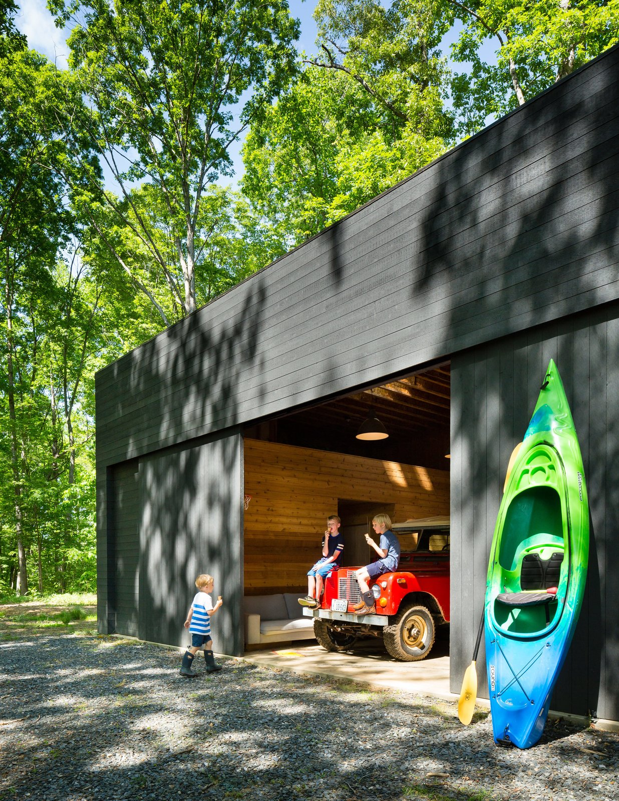 The spacious detached garage stows a bevy of kayaks and inner tubes, not to mention the family car.  Tagged: Garage.  Photo 4 of 9 in Three Joined Cabins Turn This Virginia Retreat Into a Modern Take on Camp