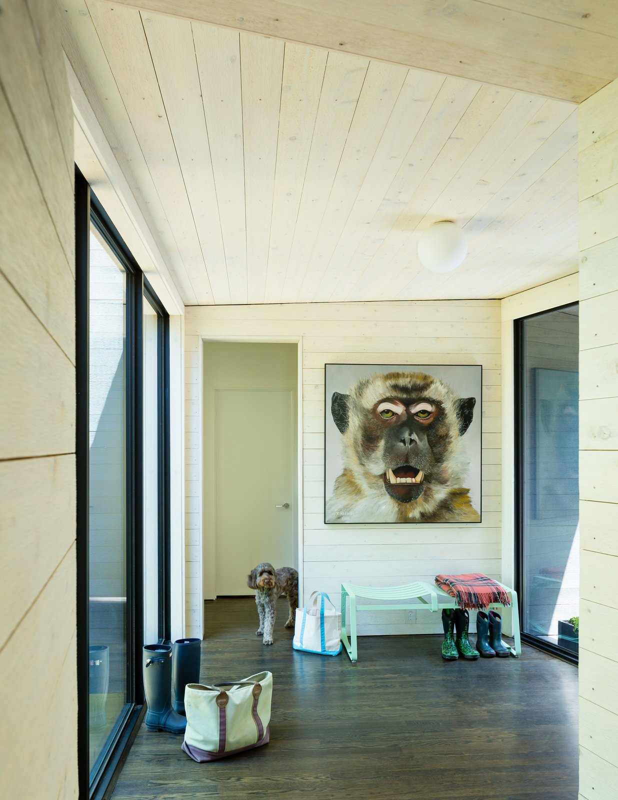 ARCHITECTUREFIRM used rough-sawn cedar paneling throughout, cladding the exterior with blackened pieces, and whitewashing the interior surfaces to form a dramatic visual contrast between inside and out. A painting by artist Tim Harriss hangs above a Crane bench by Double Butter near the entry hall Tagged: Hallway and Medium Hardwood Floor. Three Joined Cabins Turn This Virginia Retreat Into a Modern Take on Camp - Photo 5 of 9