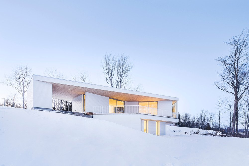 Squinting through Quebec's seasonal fluries, one might not immediately register the Nook Residence, an all-white retreat that purposefully blends into the winter landscape. The house, designed by MU Architecture, presents itself to passersby as a blank monolith, yet around the corner, it opens onto Lake Memphremagog through expansive windows and an interior balcony.  Photo 1 of 4 in This Snowbound Pad Will Actually Make You Miss Winter