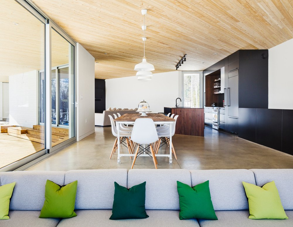 A sober material palette, including polished concrete radiant floors and black ceramic tiles, defines the interiors. The cedar ceilings extend outdoors for continuity. Tagged: Dining Room, Concrete Floor, Chair, Table, and Pendant Lighting.  Photo 4 of 4 in This Snowbound Pad Will Actually Make You Miss Winter