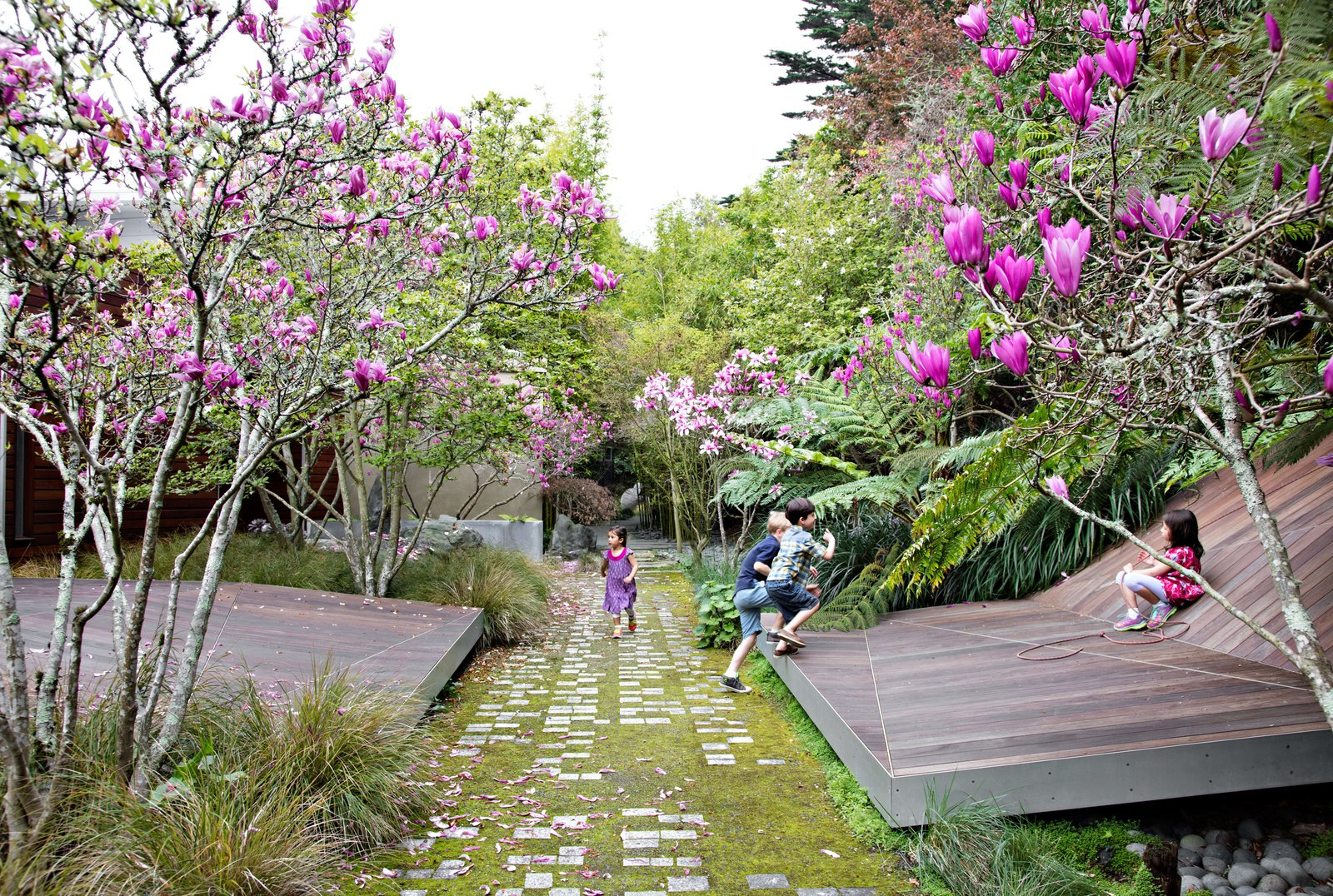 Faceted forms clad in ipe slats provide an unexpected theater for fun in Tiburon, California. The landscape, by James Lord and Roderick Wyllie of Surfacedesign, was created for a family with young children. A walkway of pavers arranged in braille spells out a poem by Christopher Marlowe; this element was conceived by local landscape architect Topher Delaney. This Endless Playscape Is Complete with a Bamboo Forest and Trampoline - Photo 2 of 11